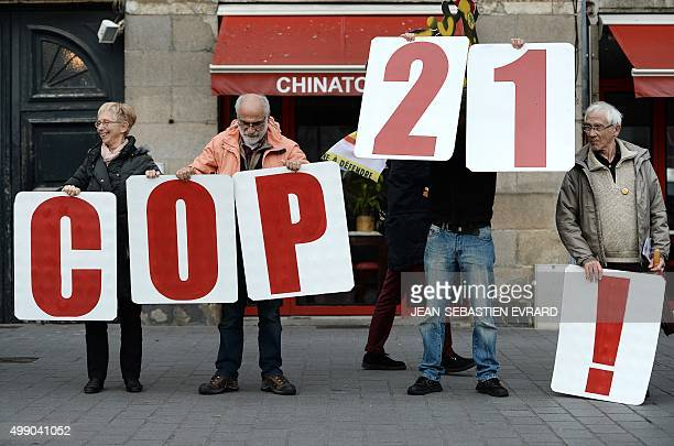 People hold signs reading 'COP21' as they form a human chain in Nantes western France on November 28 2015 during a protest called by various parties...