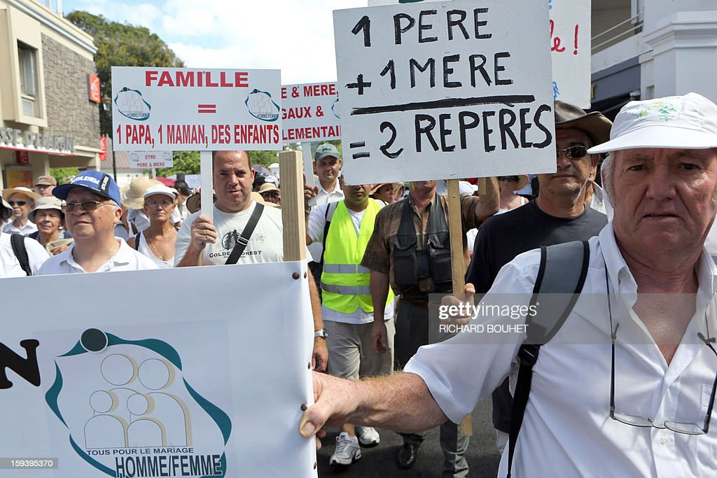 People hold signs reading (at left) '' Family= one dad, one mom, chidlren'' and '' one father +one mother = 2 markers'' during a protest against same-sex marriage, on January 13, 2013 in Saint-Denis de la Reunion, on the French Indian Ocean island of Reunion. Tens of thousands march in Paris on January 13 to denounce government plans to legalise same-sex marriage and adoption which have angered many Catholics and Muslims, France's two main faiths, as well as the right-wing opposition. The French parliament is to debate the bill -- one of the key electoral pledges of Socialist President -- at the end of this month. AFP PHOTO/RICHARD BOUHET