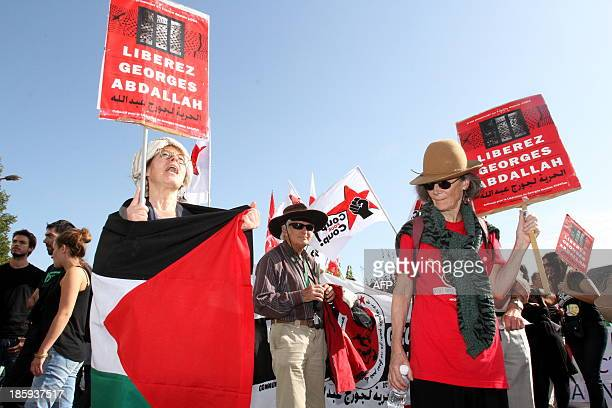 People hold signs reading 'Liberate Georges Abdallah' as they take part in a protest calling for the liberation of Lebanese activist Georges Ibrahim...