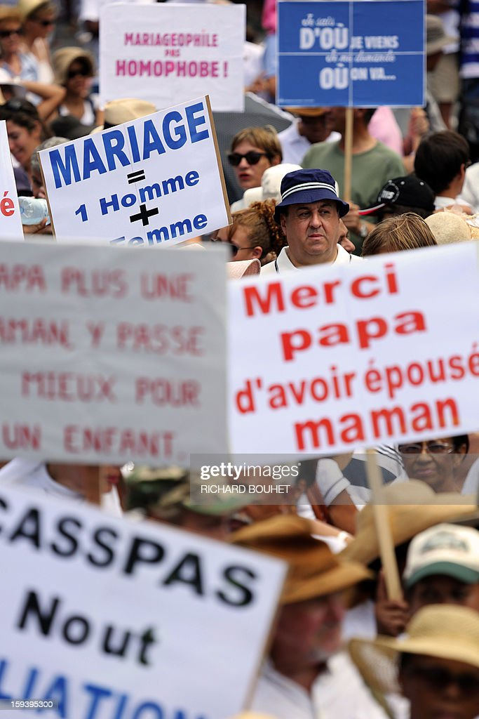 People hold signs reading (at left) '' marriage= 1 man+ 1 woman'' and '' thanks papa for marrying mom'' (at right) during a protest against same-sex marriage, on January 13, 2013 in Saint-Denis de la Reunion, on the French Indian Ocean island of Reunion. Tens of thousands march in Paris on January 13 to denounce government plans to legalise same-sex marriage and adoption which have angered many Catholics and Muslims, France's two main faiths, as well as the right-wing opposition. The French parliament is to debate the bill -- one of the key electoral pledges of Socialist President -- at the end of this month.