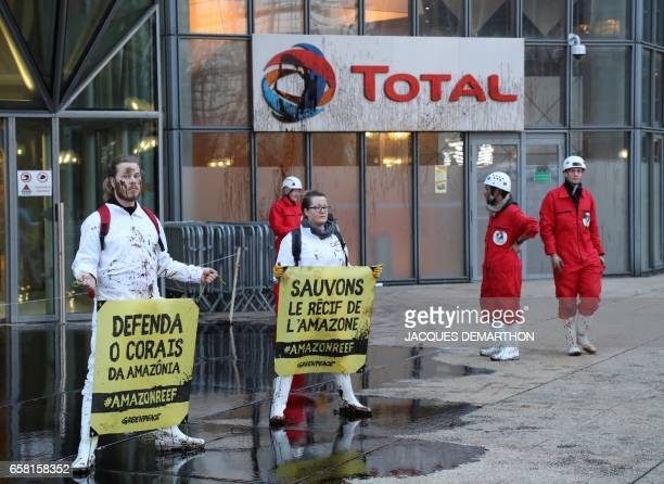 People hold signs reading 'Save Amazon reef' as Greenpeace activisits pour molasse in front of French oil giant Total headquarters on March 27 2017...