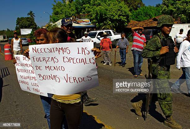 People hold signs reading 'We need the special forces of Mexico green berets' as they protest in BuenavistaTomatlan Michoacan State Mexico on January...