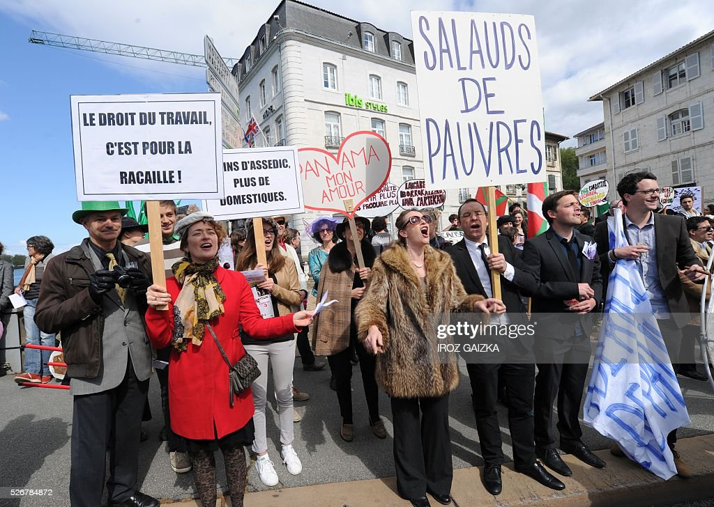 People hold signs reading 'Workers' rights are for scum' (L) and 'The stinking poor' (R) as members of the movement 'Bizi !' ('live' in Basque) stage a 'Rich peoples protest' to mark May Day in Bayonne on May 1, 2016. / AFP / IROZ