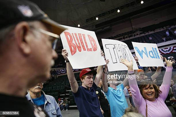 People hold signs that read ' Build that Wall' as they wait for the start of a campaign rally for Republican presidential candidate Donald Trump at...