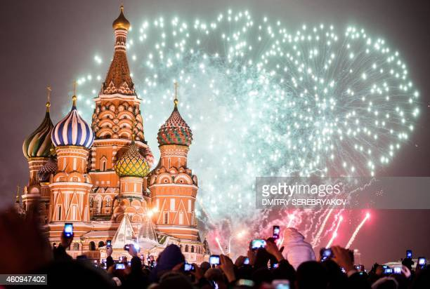 People hold smartphones as they watch fireworks during New Year celebrations at the Red square in Moscow early on January 1 2015 AFP PHOTO / DMITRY...