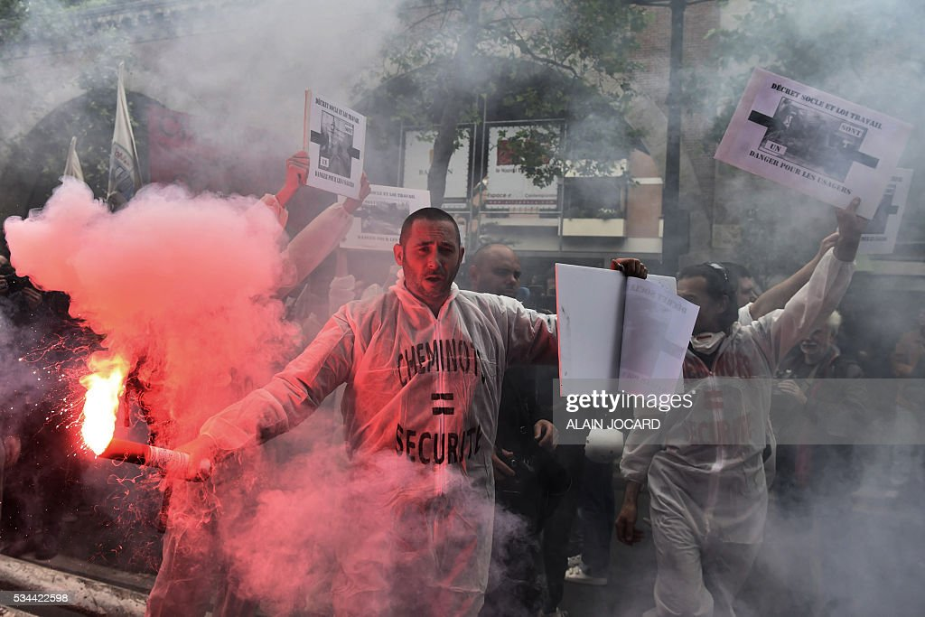 People hold smoke grenades during a protest against the government's labour market reforms in Paris, on May 26, 2016. The French government's labour market proposals, which are designed to make it easier for companies to hire and fire, have sparked a series of nationwide protests and strikes over the past three months.