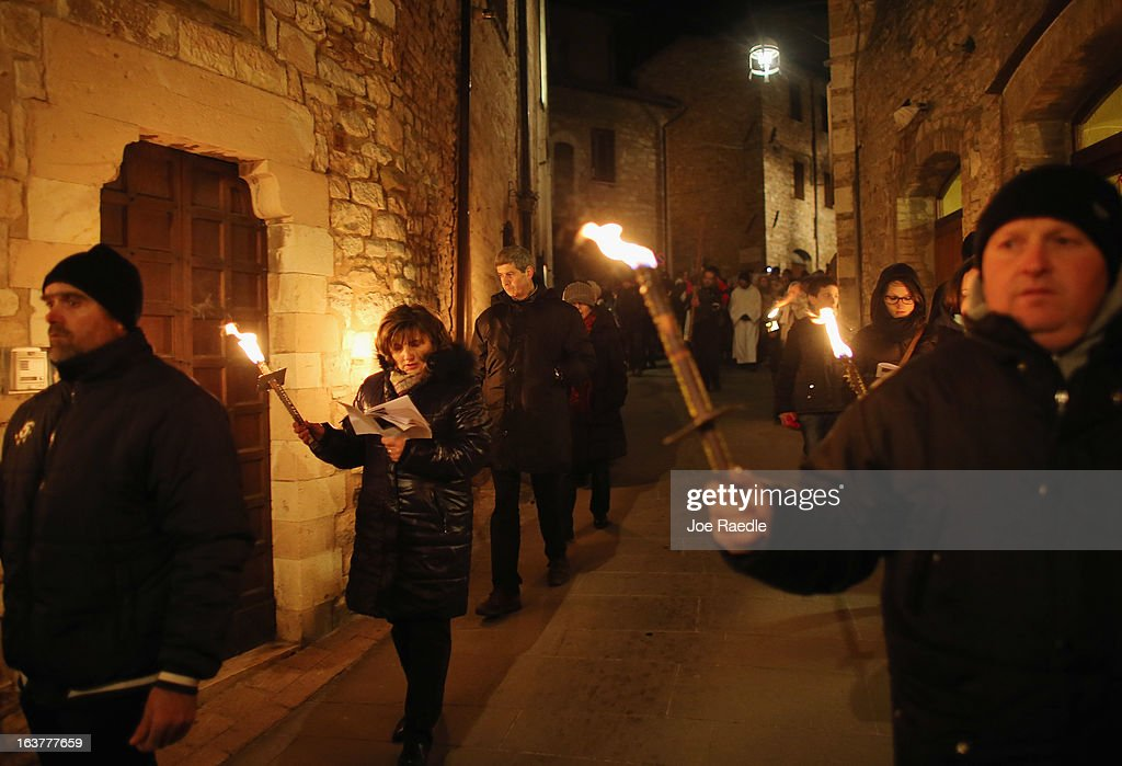 People hold torches as they walk in a religious procession through the streets of the hometown of Saint Francis of Assisi on March 15, 2013 in Assisi, Italy. Cardinal Jorge Mario Begoglio took the name Pope Francis after Saint Francis of Assisi who had renounced a life of privilege, by giving away all his possessions, wearing coarse woolen clothes and living in a humble hut after he took a vow of poverty.