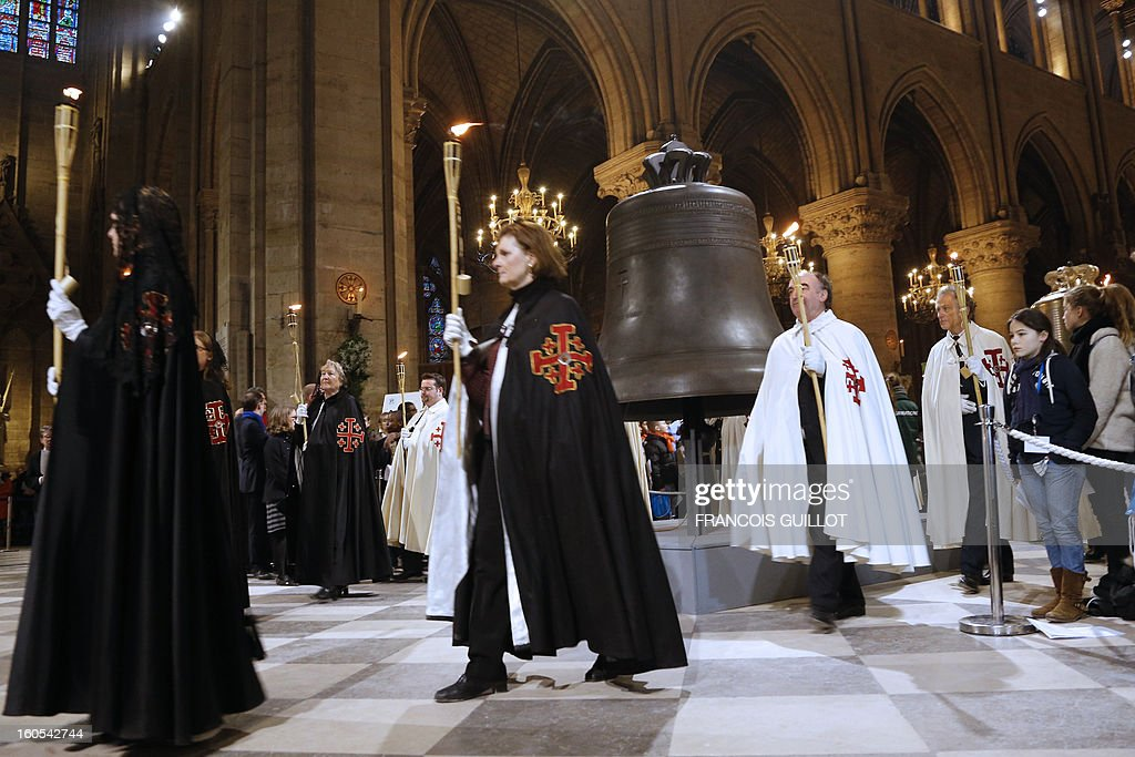 People hold torchs as they walk by the new bells of Notre-Dame de Paris Cathedral during its blessing mass on February 2, 2013 in Paris. The bell on the picture, the biggest among the nine new ones, has been made in the Dutch Royal Eijbouts foundry in Asten. Baptised 'Marie,' it weighs 6 tons and plays a G sharp note (sol diese). AFP PHOTO / FRANCOIS GUILLOT