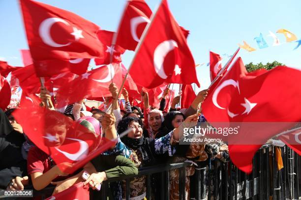 People hold Turkish flags as Turkish President Recep Tayyip Erdogan speaks the crowd at Ceylanpinar district of Sanliurfa Turkey on June 23 2017
