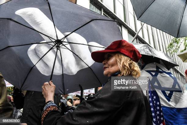 People hold umbrellas and flags as part of an Alt Right protest of Muslim Activist Linda Sarsour on April 25 2017 in New York City
