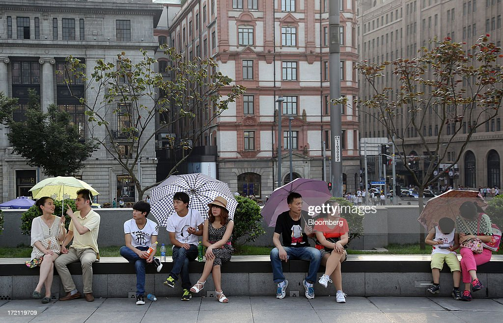 People hold umbrellas as they sit on a bench in the Bund area of Shanghai, China, on Sunday, June 30, 2013. China's President Xi Jinping said officials shouldn't be judged solely on their record in boosting gross domestic product, the latest signal that policy makers are prepared to tolerate slower economic expansion. Photographer: Tomohiro Ohsumi/Bloomberg via Getty Images