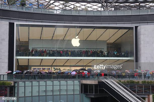 People hold umbrellas as they wait for the opening of new Apple Store in the rain on January 28 2016 in Guangzhou China Guangzhou welcomes its first...
