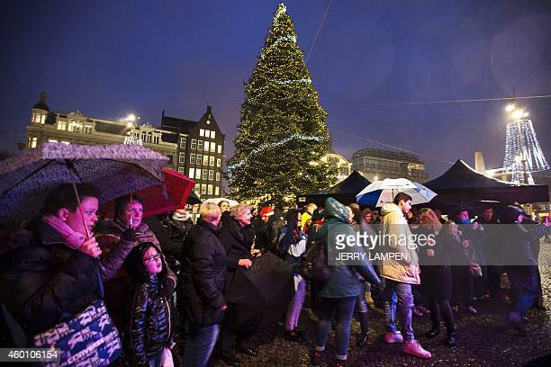 People hold umbrellas under the rain during the lighting of the Christmas tree on Dam Square in Amsterdam the Netherlands on December 7 2014 AFP...