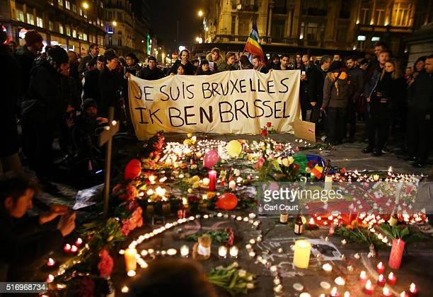 People hold up a banner as a mark of solidarity at the Place de la Bourse following today's attacks on March 22 2016 in Brussels Belgium At least 31...
