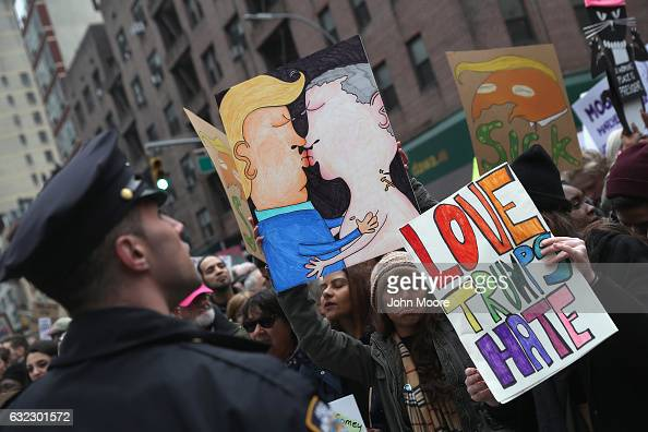 People hold up a drawing of Donald Trump and Vladimir Putin kissing while taking of part in the Women's March on January 21 2017 in New York City The...