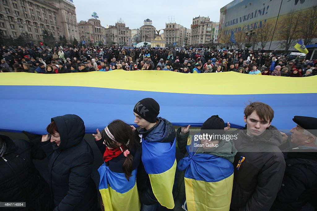 People hold up a giant Ukrainian flag following ceremonies marking the first anniversary of the Maidan revolution that led to the ouster of Ukrainian President Viktor Yanukovich one year ago at Maidan Independence Square on February 22, 2015 in Kiev, Ukraine. Tens of thousands as well as several European heads of state attended the event. Meanwhile Ukrainian government forces and pro-Russian separatists have exchanged prisoners in a promising sign that the recent Minsk ceasefire agreements might still have a chance.