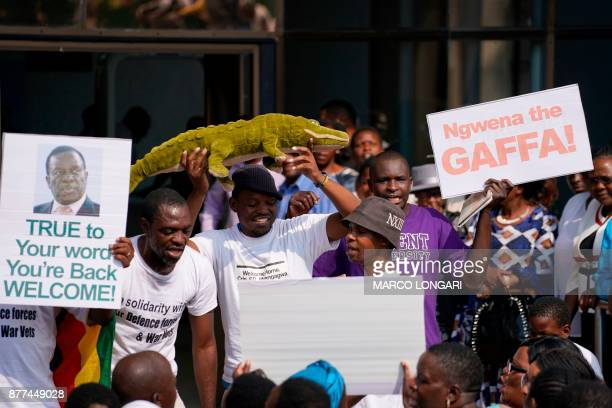 People hold up a placard reading 'True to your word you're back welcome' as they wait for the arrival of Zimbabwe's former vice president and...
