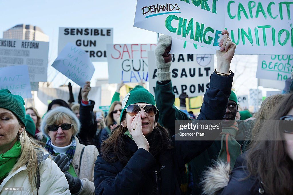 People hold up a signs during a rally at the Connecticut State Capital to promote gun control legislation in the wake of the December 14, 2012, school shooting in Newtown on February 14, 2013 in Hartford, Connecticut. Referred to as the 'March for Change' and held on the two-month anniversary of the massacre in Newtown, Connecticut, participants called for improved gun safety laws. Among the safety measures being demanded are for universal background checks, more work within the mental health community and restricting high-capacity magazines.