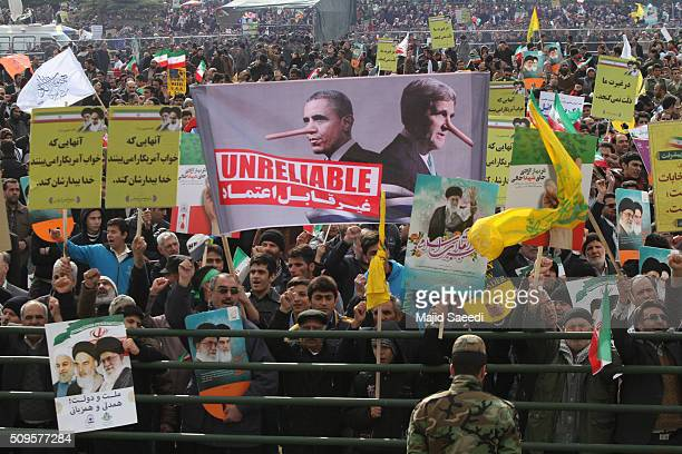 People hold up an antiUS banner at a rally to mark the 37th anniversary of the Islamic revolution in Azadi Square on February 11 2016 in Tehran Iran...