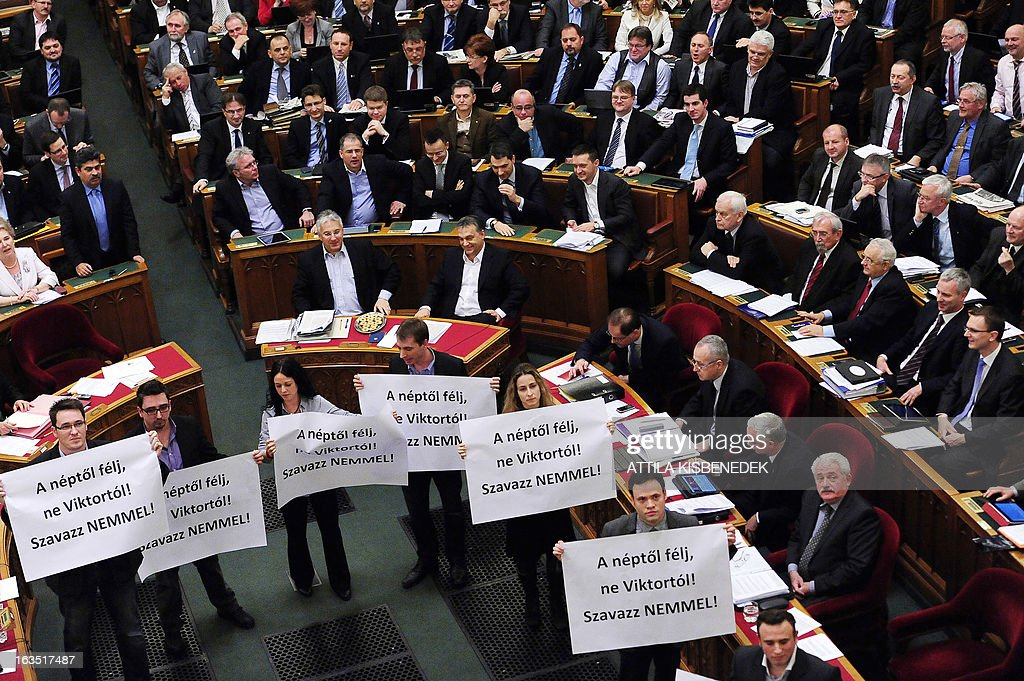 People hold up banners reading 'Vote no' next to Hungarian Prime Minister Viktor Orban (5th R) during the parliamentary session to vote on changes to the constitution on March 11, 2013 in Budapest. The Hungarian Parliament adopted the fourth modification of the basic law with 265 votes in favour, 11 against and 33 member abstaining. The changes, which have also sparked protests in Budapest, include a curb on the power of the constitutional court and reintroduce controversial measures rendered void by the court in recent months.