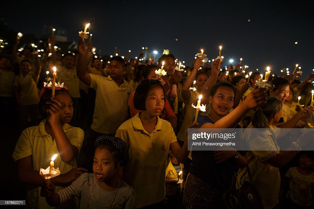 People hold up candles and sing a song honoring King Bhumibol Adulyadej during a ceremony celebrating the King's birthday at Royal Ground on December 5, 2012 in Bangkok, Thailand. The King of Thailand, His Majesty King Bhumibol Adulyadej was born in 1927 and celebrates his 85th birthday. Tens of thousands come to pay respect and get a rare chance to see him in person. The King has reigned since June 1946, making him the world's longest reigning current monarch and the world's longest serving head of state, it has been in continuous existence since the founding of the Kingdom of Sukhothai in 1238. Supporters wear yellow representing Monday, the birthday of His Majesty the King. The king's power is limited to being a symbolic figurehead, commanding the respect and reverence of the Thai people.