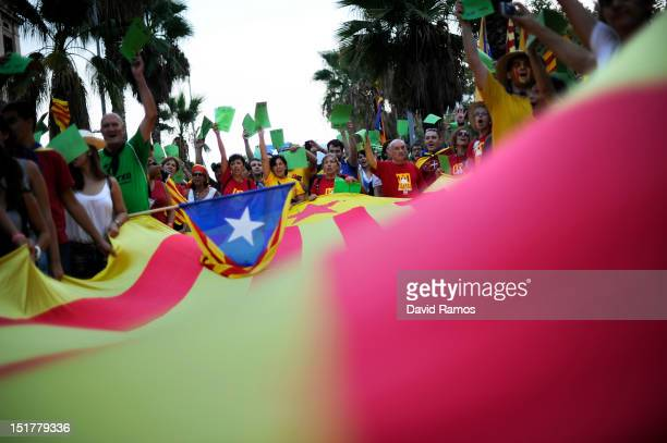 People hold up green ballot cards for in favour of Catalonia's independence during a demonstration calling for independence during the Catalonia's...