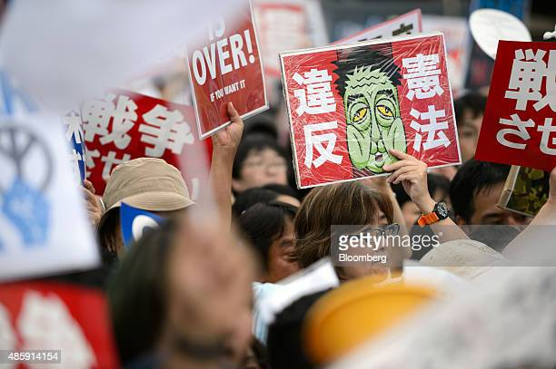 People hold up placards as they take part in a protest against Japanese Prime Minister Shinzo Abe's security bills outside the National Diet building...