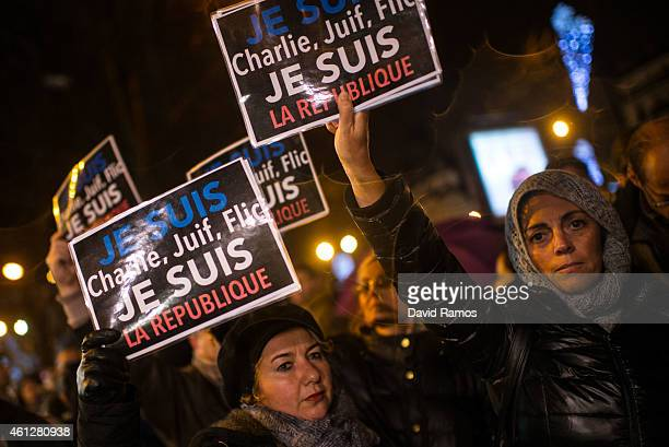 People hold up placarts reading 'Je suis Charlie Juif Flic Je suis la Republique' at the site of the attack on a kosher market on January 10 2015 in...