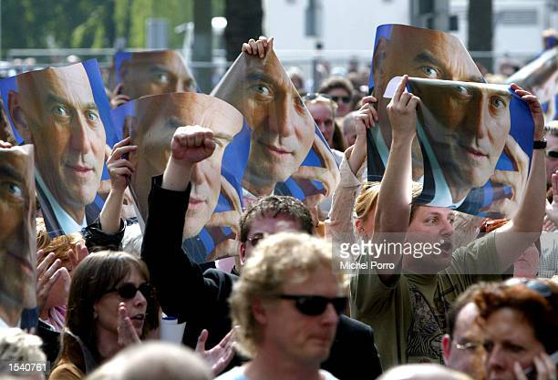 People hold up posters of slain politician Pim Fortuyn as they wait to pay their respects May 9 2002 in Rotterdam Netherlands Thousands of people...
