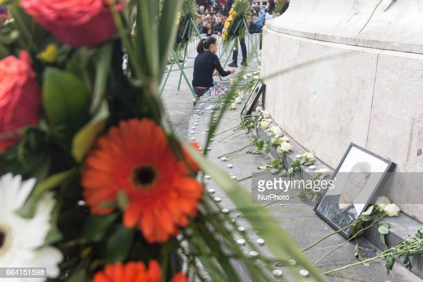 People hold up roses as they gather at Place de la Republique in Paris France on April 2 to mourn the death of Shaoyao Liu during a police...