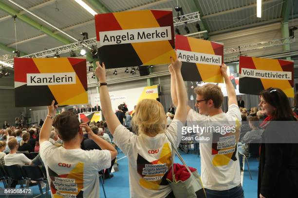 People hold up signs as they listen to German Chancellor and Christian Democrat Angela Merkel speak at an election campaign stop on September 19 2017...