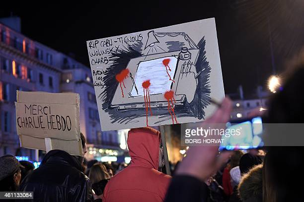 People hold up signs that read in French ' Thank you Charlie Hebdo' and 'RIP Cabu Tignous Wolinski Chard ' as they rally to pay tribute in Marseille...