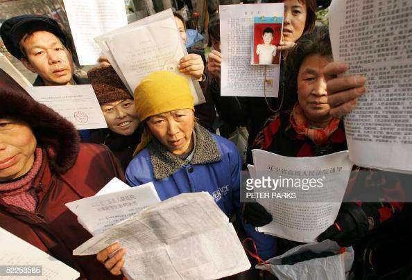 People hold up their petitions in a squatter village in southern Beijing 01 March 2005 where people from all over China have come to air their...