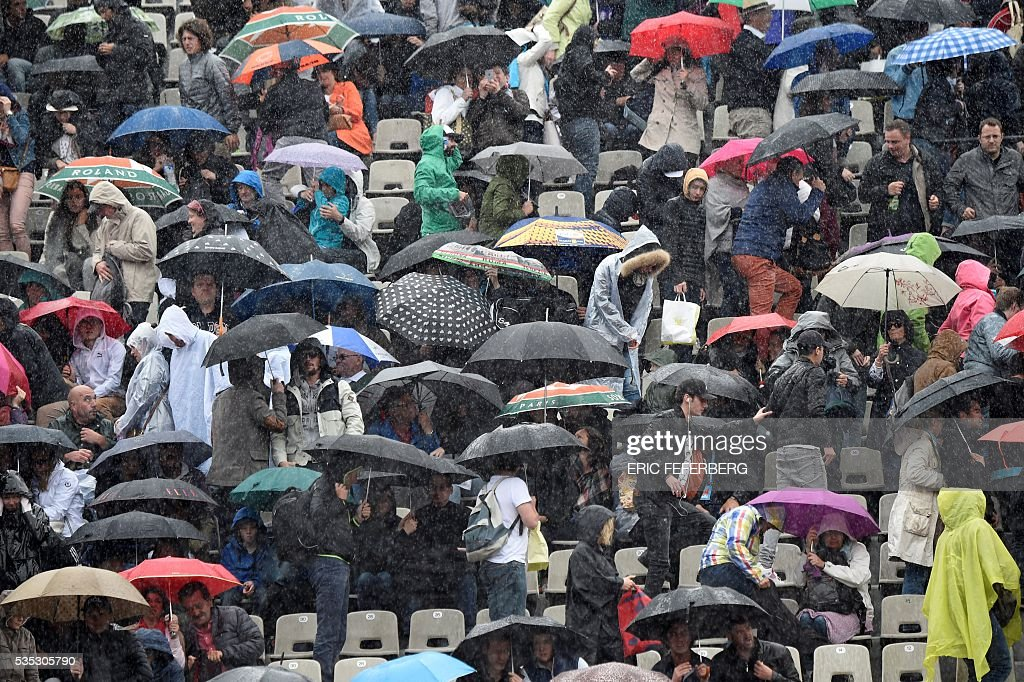 People hold up umbrellas as play is interrupted due to rain at the Roland Garros 2016 French Tennis Open in Paris on May 29, 2016. / AFP / Eric FEFERBERG