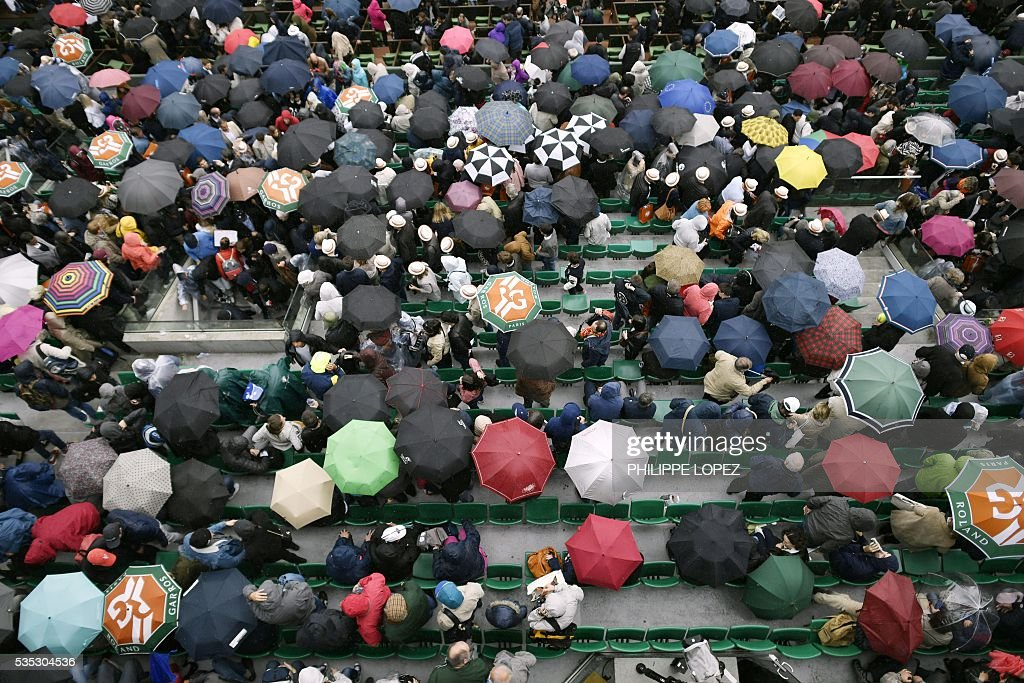 People hold up umbrellas as rain interrupts play during the men's fourth round match between France's Richard Gasquet and Japan's Kei Nishikori at the Roland Garros 2016 French Tennis Open in Paris on May 29, 2016. / AFP / PHILIPPE