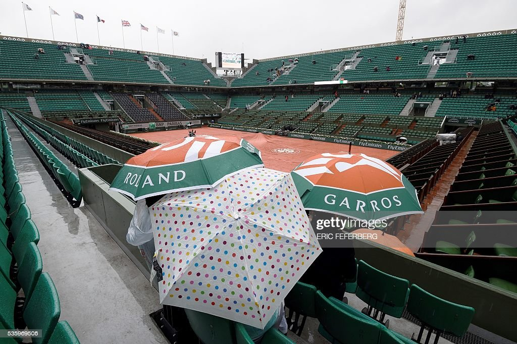 People hold up umbrellas as rains falls over the Roland Garros stadium during the Roland Garros 2016 French Tennis Open in Paris on May 31, 2016. / AFP / Eric FEFERBERG