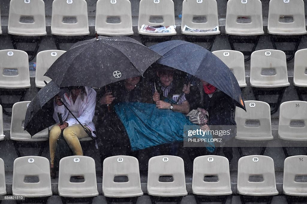 People hold up umbrellas in the stands as rain interrupts play during the women's third round match between the US's Venus Williams and France's Alize Cornet at the Roland Garros 2016 French Tennis Open in Paris on May 28, 2016. / AFP / PHILIPPE