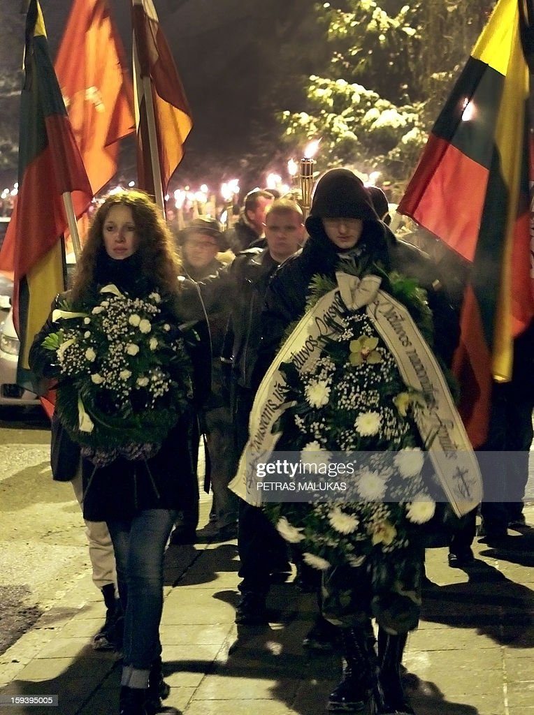 People hold wreaths during a 'January Event' commemoration ceremony at the Antakalnis cemetery in Vilnius on January 12, 2013. Victims of the so called 'January Events' of 1991 are buried at the cemetary. On January 13, 1991 Soviet troops tried to crush the new Lithuanian state.