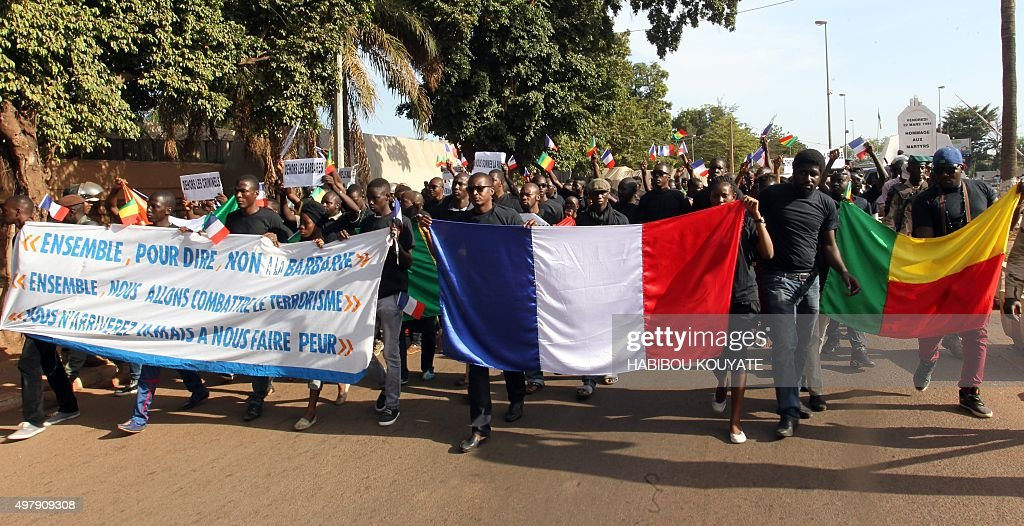 People holding a banner reading 'Together to say no to barbarism Together we will fight terrorism You will never scare us' France's and Benin's flags...