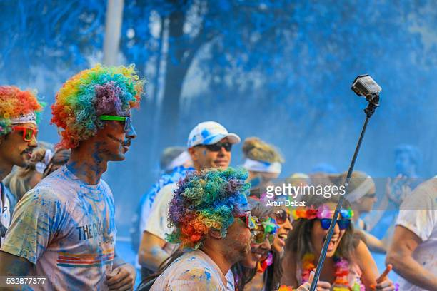 People holding a Gopro attached to a selfie stick taking pictures himself during the Color Run with colorful Gulal in Barcelona city