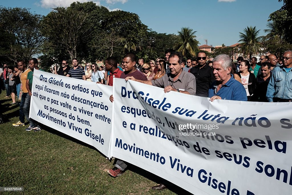 People holding banners attend the funeral of doctor Gisele Palhares Gouvea -who was murdered on June 25- in Rio de Janeiro, Brazil, on June 27, 2016. Brazilian 34-year-old doctor Gisele Palhares Gouvea was shot in the head inside her SUV, as she drove home after attending the inauguration of the service center for handicapped people in northern Rio de Janeiro. / AFP / YASUYOSHI