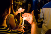 Group of people holding candle vigil in darkness seeking hope, worship, prayer