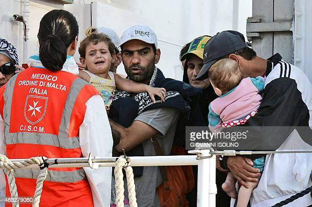 People holding children wait to disembark the patrol vessel Fiorillo of the Italian Coast Guard as it arrives in the port of Pozzallo on August 7...