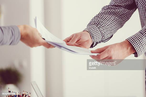 People holding documents, close up of hands