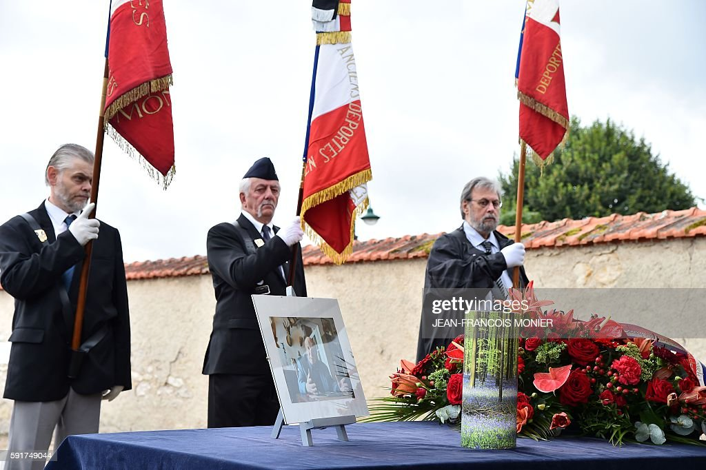 People holding flags pay honor next to a picture and the funerary urn of Georges Seguy former secretary general of French major union CGT during his...
