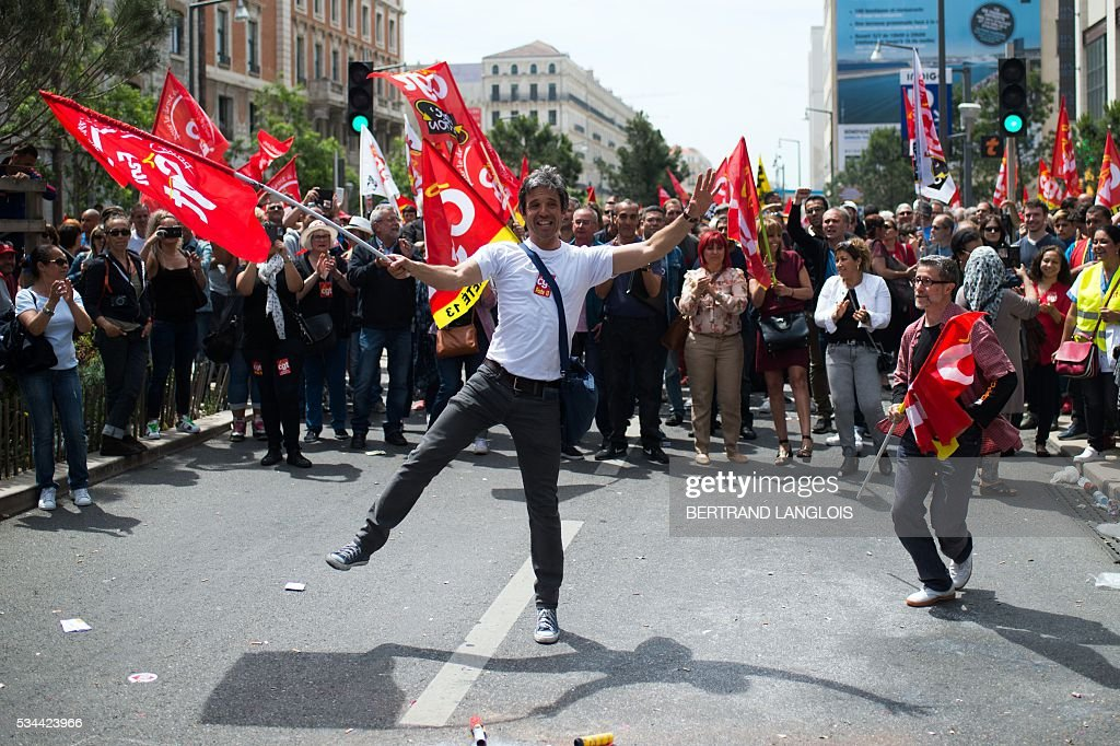 People holding French CGT union take part in a demonstration against the French government's planned labour law reforms in front of Les Terrasses du Port commercial centre on May 26, 2016 in Marseille. The French government's labour market proposals, which are designed to make it easier for companies to hire and fire, have sparked a series of nationwide protests and strikes over the past three months. / AFP / BERTRAND
