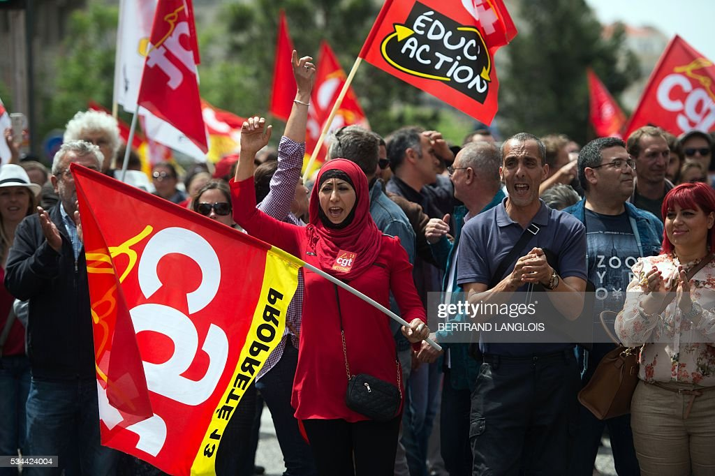 People holding French CGT union's flag take part in a demonstration against the French government's planned labour law reforms in front of Les Terrasses du Port commercial centre on May 26, 2016 in Marseille. The French government's labour market proposals, which are designed to make it easier for companies to hire and fire, have sparked a series of nationwide protests and strikes over the past three months. / AFP / BERTRAND