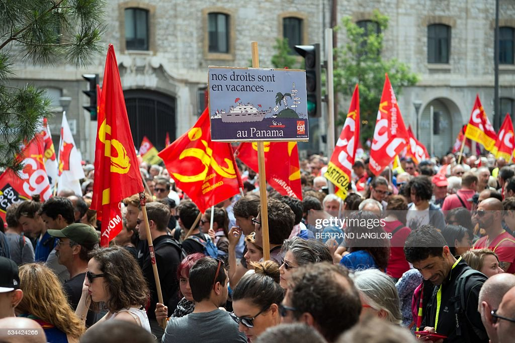 People holding French CGT union's flags take part in a demonstration during a demonstration against the French government's planned labour law reforms in front of Les Terrasses du Port commercial centre on May 26, 2016 in Marseille. The French government's labour market proposals, which are designed to make it easier for companies to hire and fire, have sparked a series of nationwide protests and strikes over the past three months. The sign reads 'Our rights are on holidays in Panama'. / AFP / BERTRAND