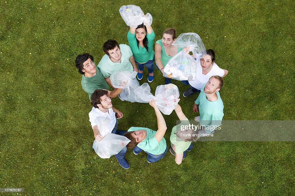 People holding garbage bags on grass : Stock Photo