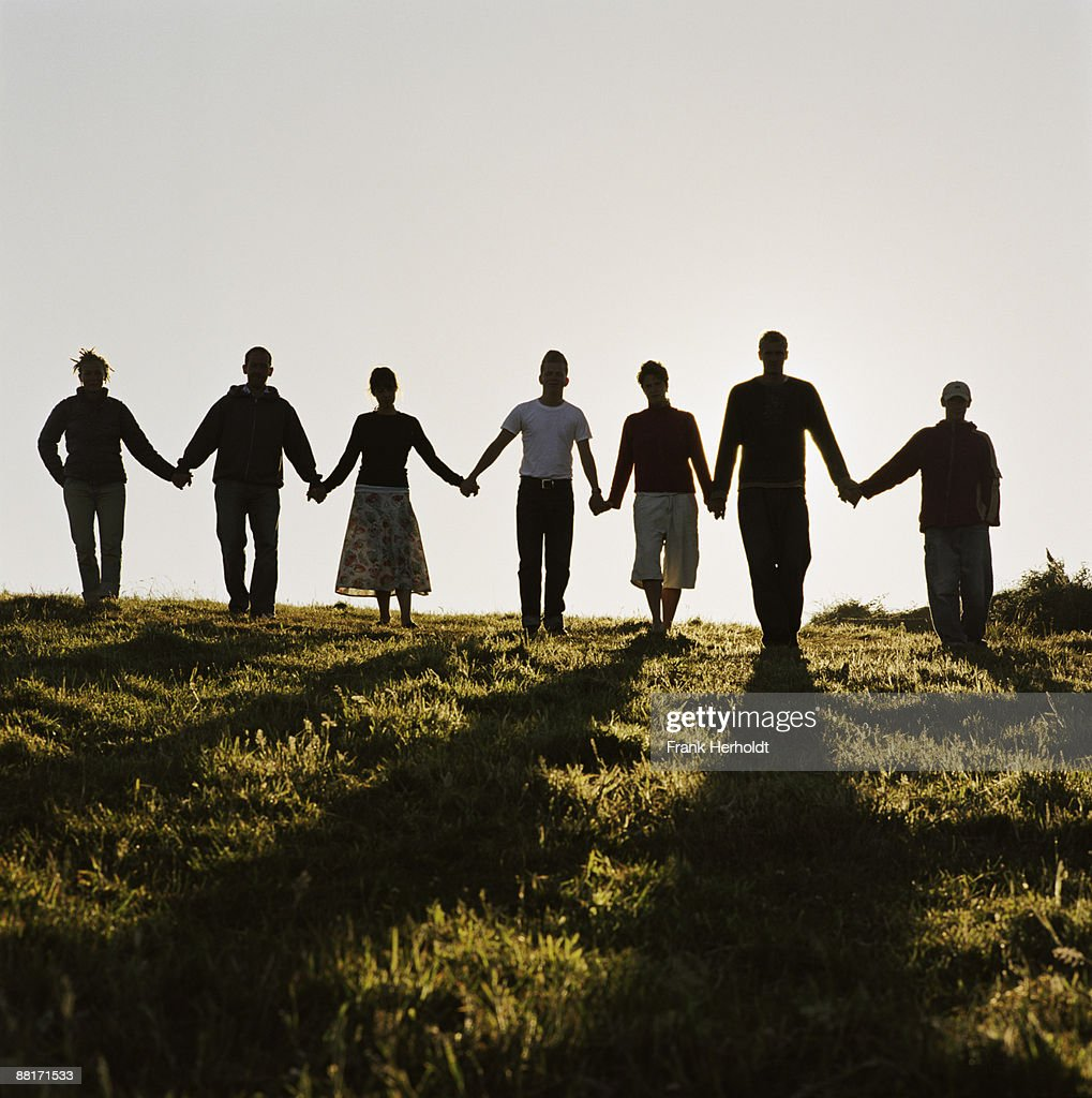 People holding hands in field